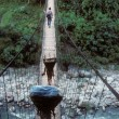 Stock Photo: Porters carrying loads across suspension bridge