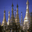 Golden spires of Buddhist stupas in temple — Stock Photo #13509149