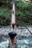 Porters carrying loads across suspension bridge — Stock Photo