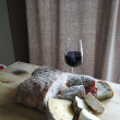 Glass of red wine, salami, cheese and whole grain bread — Stock Photo #13510179
