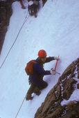 Climber on ice headwall of glacier — Stock Photo