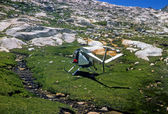 Rescue helicopter taking off from high mountain meadow — Stock Photo