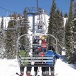 Skiers ride the chairlift through a spruce forest — Stockfoto