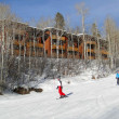 Skiers slide past expensive townhouses — Stock Photo