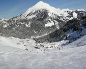 Skiers descend to tiny mountain village — Stock Photo