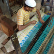 Young muslim man runs a loom — Stockfoto