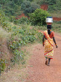 Tribal women carry goods on their heads — Stock Photo