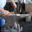 Stock Photo: Blacksmith hammers nails