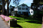 Colorful flowers and classic New England home — Stock Photo