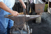 Blacksmith hammers nails — Stock Photo