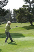 Woman golfer teeing off — Stock Photo
