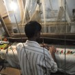 Stock Photo: Young muslim mruns loom to weave silk brocade