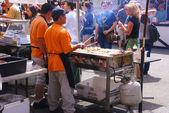 Asiatische Köche servieren von concessions. — Stockfoto
