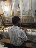 Young muslim man runs a loom to weave silk brocade — Stock Photo