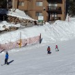 Stockfoto: Ski instructor guides children down mountain