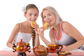 Mother and daughter eating pies — Stock Photo