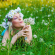 Young woman blowing a dandelion on fields — Stock Photo #23467428