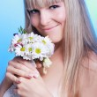 Beautiful young woman in a white dress with a bouquet of flowers — Stock Photo
