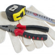 Stock Photo: Pliers red and black color, dirty leather gloves and tape measur