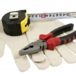 Pliers red and black color, dirty leather gloves and tape measur — Stock Photo