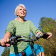 Mature woman with bicycle — Stock Photo #13303365