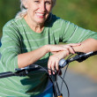Mature woman with bicycle - Stock Photo