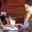 Portrait of successful young woman with laptop in street cafe — Stock Photo