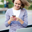 Young woman with laptop and cell phone — Stock Photo