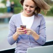 Stock Photo: Young woman with laptop and cell phone
