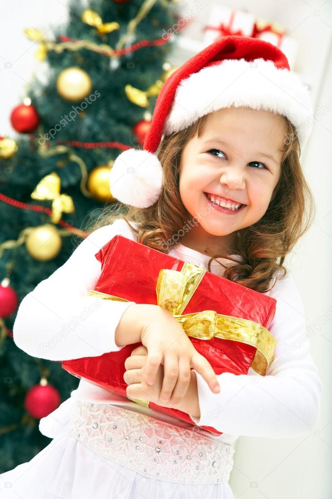 Portrait of little cute girl with Christmas present — Stock Photo #13806080