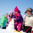 Happy family making snowman — Stock Photo