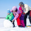 Happy family making snowman — Stock Photo #14535957