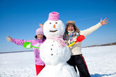 Happy couple with snowman — Stock Photo
