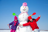 Happy family with snowman — Stock Photo