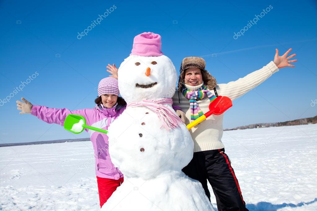 Portrait of happy couple with big snowman blue sky background — Stock Photo #14535967