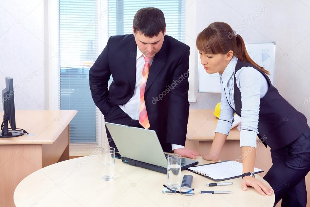 businesspeople are discussing in the office behind a desk with a laptop — Stock Photo #16501749