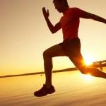 Young man running along the seashore at sunset — Stock Photo