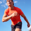 Young muscular athlete is running at the stadium background of blue sky — Stock Photo