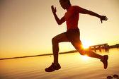 Młody człowiek biegnącej wzdłuż brzegu morza na zachód słońca — Zdjęcie stockowe