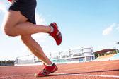 молодой спортсмен мышечной выполняется на стадион фоне голубого неба — Стоковое фото
