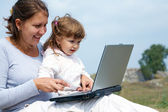 Mom and daughter and a laptop — Stock Photo
