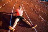 Athlete sits on the treadmill stadium — Stock Photo