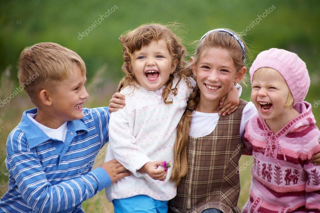 Portrait of a group of children happily laughing and playing on the grass — Stock Photo #19261525
