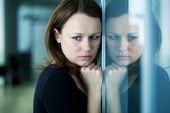Ledsen kvinna vid fönstret — Stockfoto