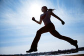 Female runner silhouette against the blue sky and sun — Stock Photo