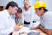 Meeting the team of engineers working on a construction project at the table — Stock Photo