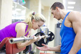 Woman with instructor in gym — Stock Photo