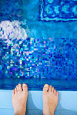 Feet on the edge of the pool — Stock Photo