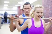 Vrouw met instructeur in de sportschool — Stockfoto