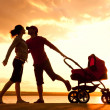 Happy family walking on sunset - Stock Photo